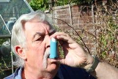Bejaarde die een astmainhaleertoestel met behulp van. Stock Fotografie