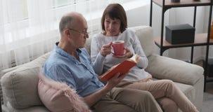 Bejaarde die een boek lezen aan zijn vrouw het drinken koffie stock videobeelden