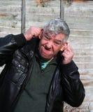Bejaarde die een grappig gezicht trekt. Stock Foto's