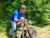 Bejaarde die een houten motorracer spelen stock foto's