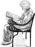 Bejaarde die een krant lezen Stock Foto's