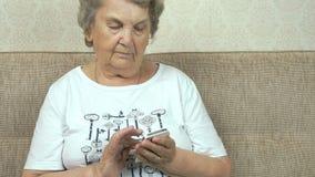 Bejaarde die een mobiele telefoon thuis houden stock video