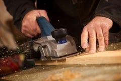Bejaarde die een plank van hout schaven stock afbeeldingen