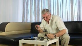 Bejaarde die een raad met een soldeerbout solderen, heeft hij in zijn handen een groot vergrootglas stock footage