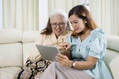 Bejaarde die een tablet met haar dochter gebruiken royalty-vrije stock foto's