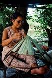 bejaarde die een traditionele kegelhoed maken bij haar huis stock fotografie