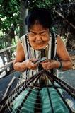 bejaarde die een traditionele kegelhoed maken bij haar huis stock afbeeldingen