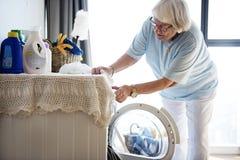 Bejaarde die een wasserij doen royalty-vrije stock afbeelding