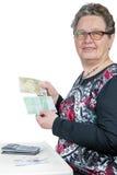 Bejaarde die en geld tellen tonen Stock Fotografie