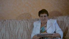 Bejaarde die foto's op uw tablet kijken stock footage