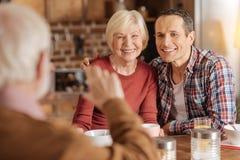 Bejaarde die foto van zijn familie nemen bij ontbijt stock foto