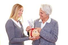Bejaarde die geld schenkt Stock Afbeeldingen