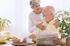 Bejaarde die glimlachende echtgenoot koesteren royalty-vrije stock foto's