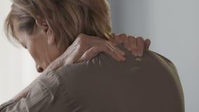 Bejaarde die haar hals en schouders masseren, voelend pijn en ongemak stock videobeelden