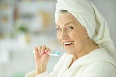 Bejaarde die haar tanden borstelen stock foto