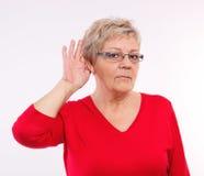 Bejaarde die hand plaatsen op oor, moeilijkheid in hoorzitting in oude dag stock fotografie
