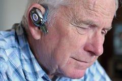 Bejaarde die hands-free apparaat van de celtelefoon draagt Royalty-vrije Stock Afbeeldingen