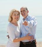 Bejaarde die iets hand tonen een vrouw op het strand Stock Foto
