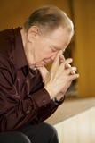 Bejaarde die in kerk bidt Stock Afbeeldingen