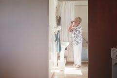 Bejaarde die klaar in badkamers worden royalty-vrije stock fotografie