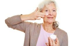Bejaarde die lotion toepassen stock foto