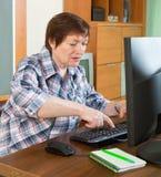 Bejaarde die met computer werken Stock Foto