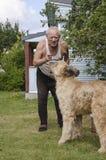 Bejaarde die met een hond spreken Royalty-vrije Stock Afbeeldingen