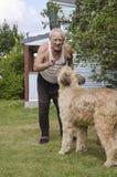 Bejaarde die met een hond spreken Stock Foto