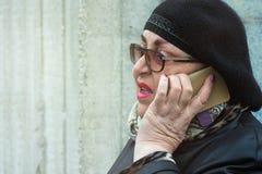 Bejaarde die met heldere make-up op de telefoon in openlucht spreken royalty-vrije stock fotografie