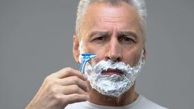 Bejaarde die met schuim op gezicht zijn baard scheren, die voor datum, hygiëne voorbereidingen treffen stock videobeelden