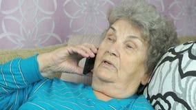 Bejaarde die met vriend op mobiele telefoon spreken stock footage