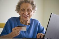 Bejaarde die online winkelt Stock Fotografie