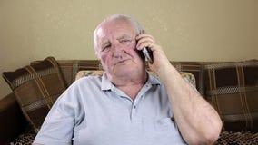 Bejaarde die op de telefoon spreken stock footage