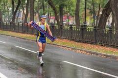 Bejaarde die op een stadsstraat lopen die banner van zijn inheemse stad Mariupol nemen tijdens 21 km-afstand van de Marathon van  royalty-vrije stock afbeelding