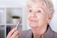 Bejaarde die op lippenstift zetten Stock Afbeeldingen