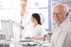 Bejaarde die op onderzoek het glimlachen wacht stock afbeelding