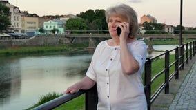 Bejaarde die op smartphone dichtbij het traliewerk op waterkant in avondtijd, oude stad, rivier en brug in spreken stock footage