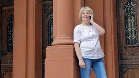 Bejaarde die op smartphone spreken De uitstekende bouw op de achtergrond stock video