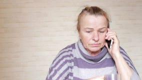 Bejaarde die op telefoon thuis spreken stock videobeelden