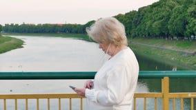 Bejaarde die over de brug over de rivier lopen en smartphone met oortelefoons gebruiken stock videobeelden