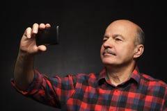 Bejaarde die selfie op een smartphone doen stock afbeeldingen