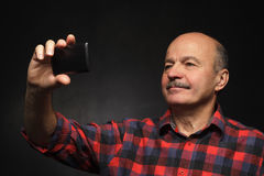Bejaarde die selfie op een smartphone doen royalty-vrije stock foto's