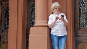 Bejaarde die smartphone met oortelefoons gebruiken De uitstekende bouw op de achtergrond stock videobeelden