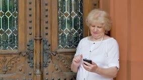 Bejaarde die smartphone met oortelefoons gebruiken De uitstekende bouw op de achtergrond stock footage