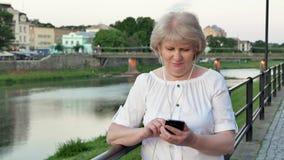 Bejaarde die smartphone met oortelefoons gebruiken dichtbij het traliewerk op waterkant in avondtijd, oude stad, rivier en brug stock videobeelden