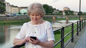 Bejaarde die smartphone met oortelefoons gebruiken dichtbij het traliewerk op waterkant in avondtijd, oude stad, rivier en brug stock video