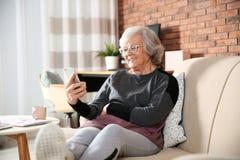 Bejaarde die smartphone op bank gebruiken stock foto's