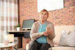 Bejaarde die smartphone op bank gebruiken royalty-vrije stock fotografie