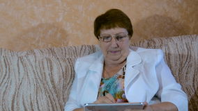 Bejaarde die tablet bestuderen stock video