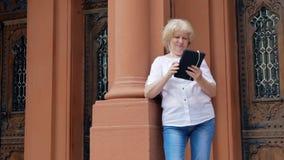 Bejaarde die tabletcomputer met oortelefoons met behulp van De uitstekende bouw op de achtergrond stock footage